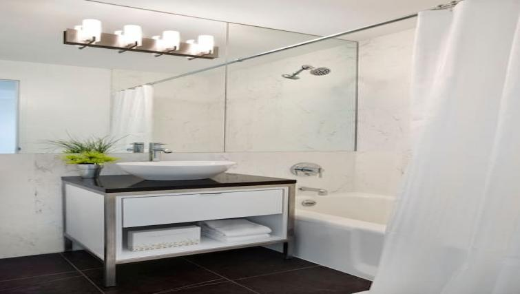Bath with above shower at Instrata Gramercy Apartments